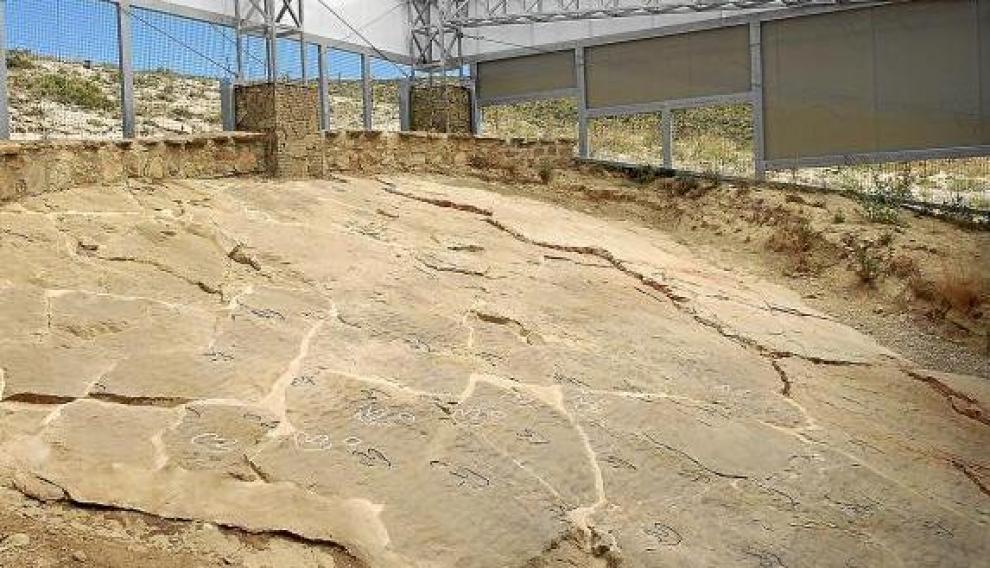 El contorno de las huellas fósiles de dinosaurio de Las Cerradicas, marcado con líneas blancas y negras.