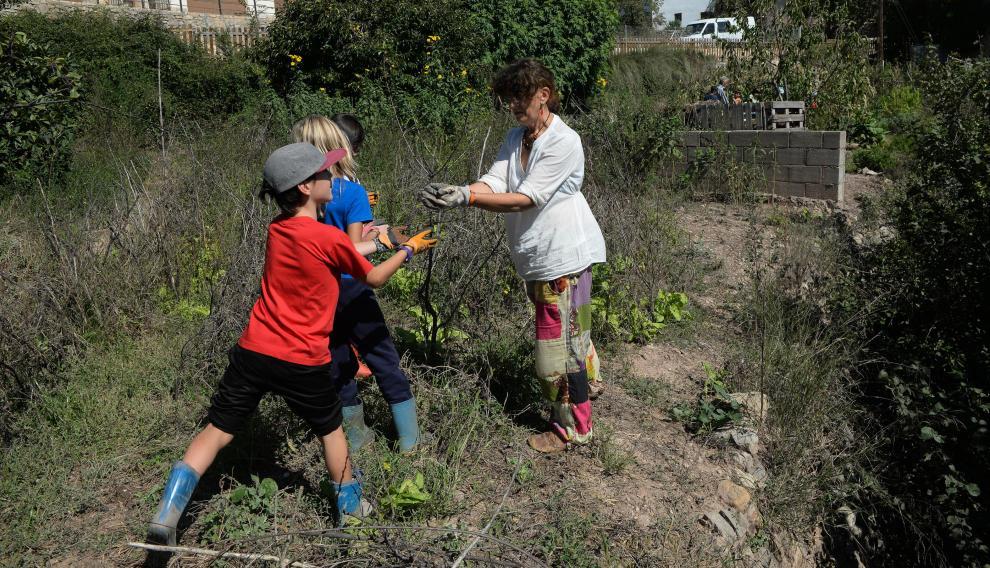 Delfi Ruiz, en el huerto de la escuela de Olba (Teruel), con tres de sus alumnos
