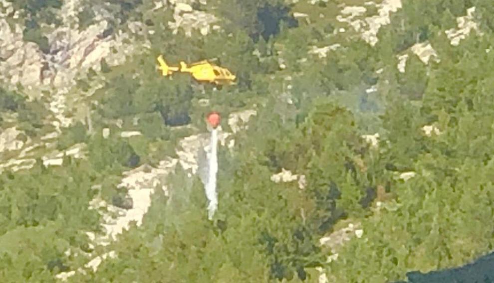 Un helicóptero arroja agua sobre una superficie arbolada para apagar un incendio en Panticosa.