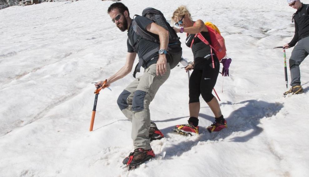 Dos montañeros equipados con piolet y crampones descienden el glaciar.