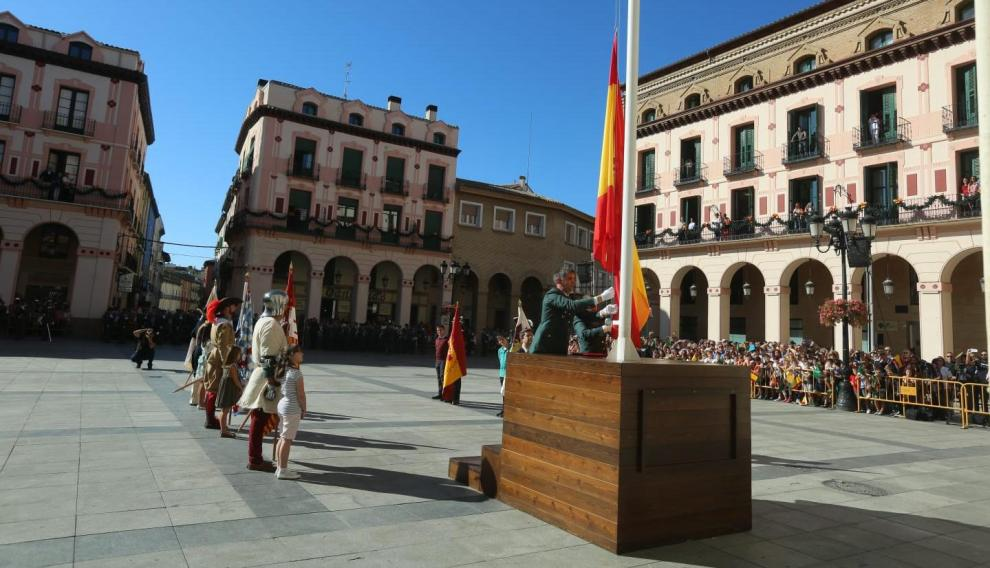 Momento del izado de la bandera nacional donada por Huesca en la plaza de Luis López Allué.