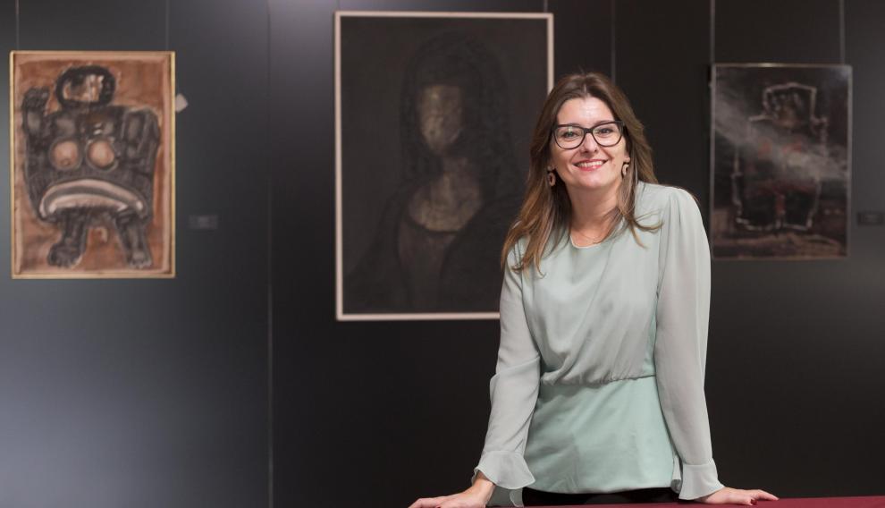 La periodista oscense Esther Puisac, junto a algunas de las obras de la exposición sobre Agustín Alamán que se pueden ver en el Casino de Huesca.