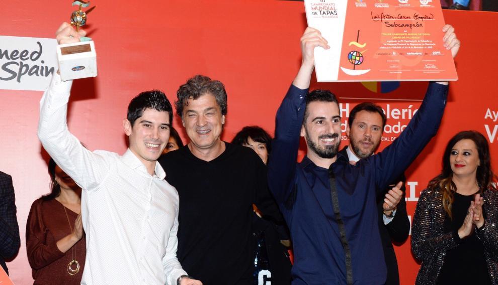 Luis Carcas alza el diploma que le acredita como subcampeón (d), y su hermano Javier (i), el trofeo.