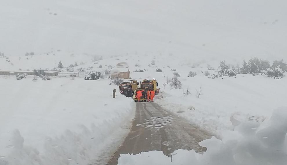 Los servicios de mantenimiento de carreteras retiran una máquina quitanieves atascada en la nieve.