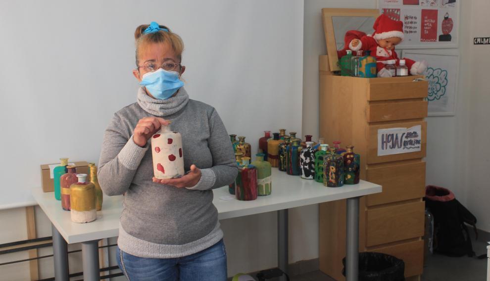 Cristina García, usuaria de Atades, enseña una de las botellas que ha decorado estos días.