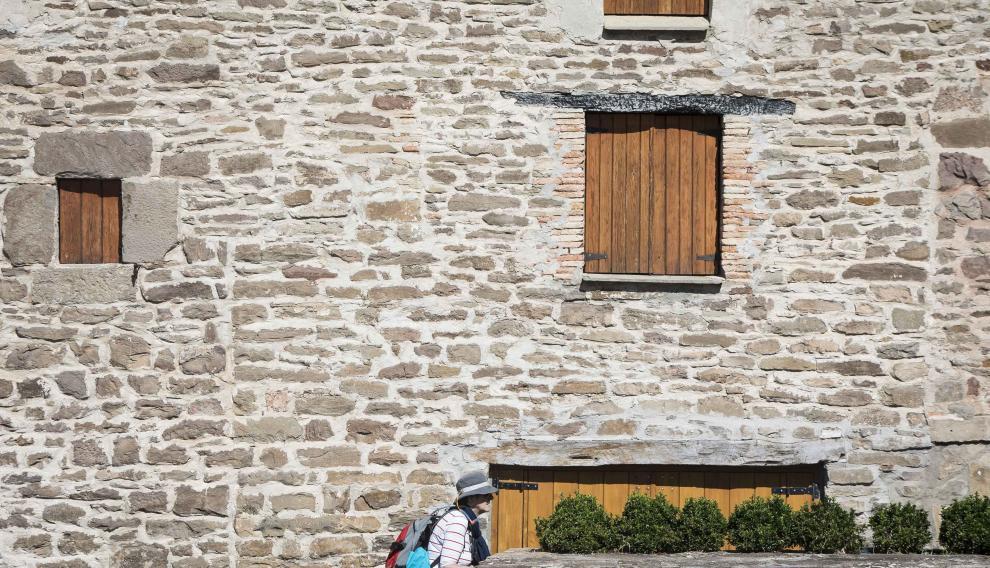 Una peregrina del Camino de Santiago se funde con el paisaje urbano de Undués de Lerda.