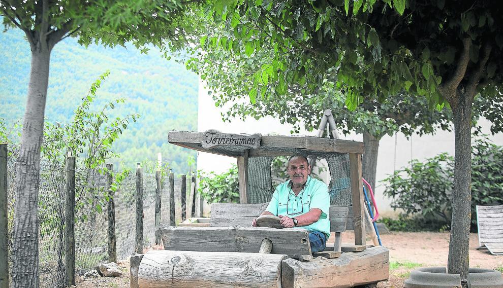 El fundador de Torrebruñac, José Román, en el troncomóvil a tamaño 'natural' que tiene en el jardín y que ha tallado él mismo.