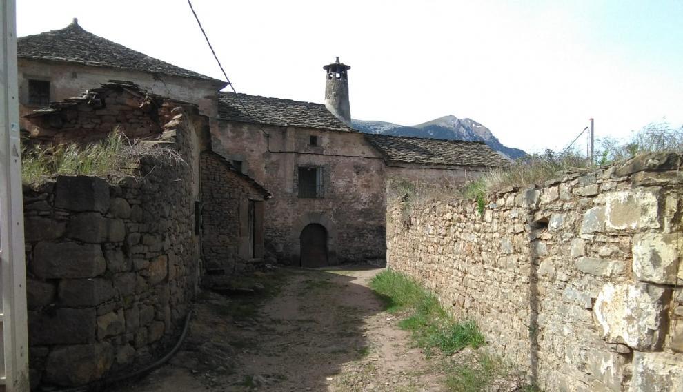 Una de las calles del pueblo y una vivienda con la tradicional chimenea.