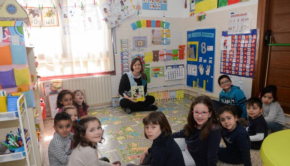 Sara Martí sentada con sus alumnos, en el aula de Valdeltormo del CRA Matarraña (Teruel), a punto de comenzar la maravillosa aventura de leer