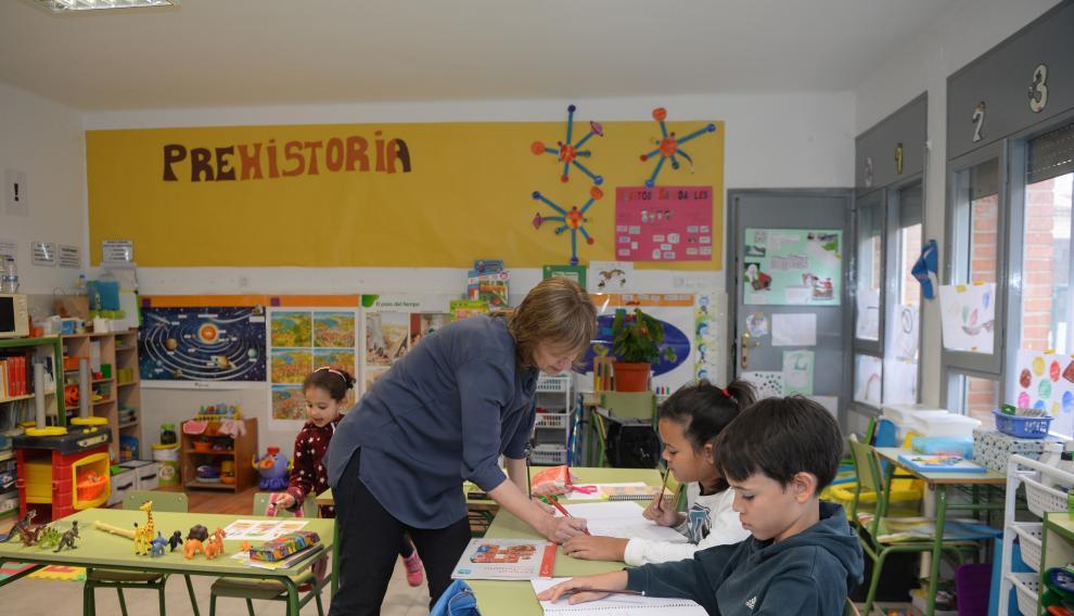Mariví con sus tres alumnos trabajando en el aula.