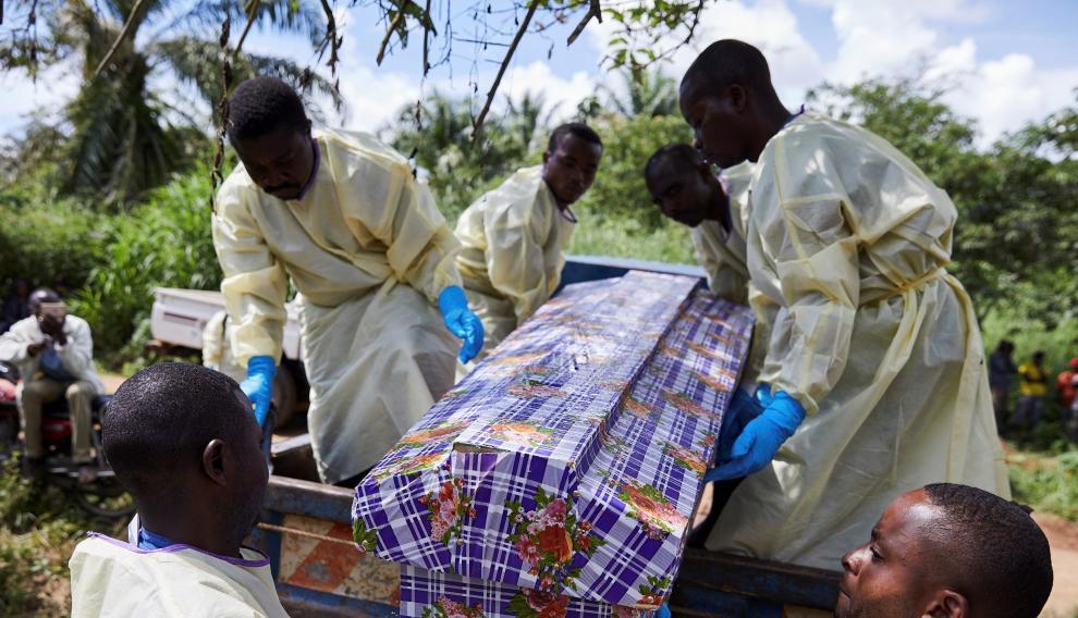 Varios trabajadores sanitarios entierran el cadáver de un hombre que se infectó con ébola tras compartir habitación con un paciente enfermo en Beni (Congo).