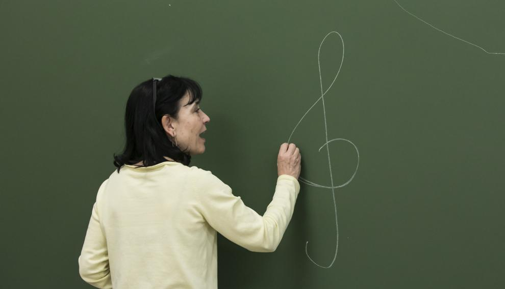 Isabel Zamora, dibujando la clave de sol, en la pizarra