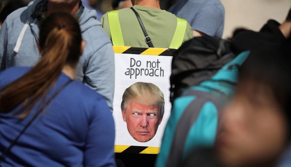 Varias personas esperan la llegada del presidente estadounidense Donald Trump en frente del Buckingham Palace de Londres.