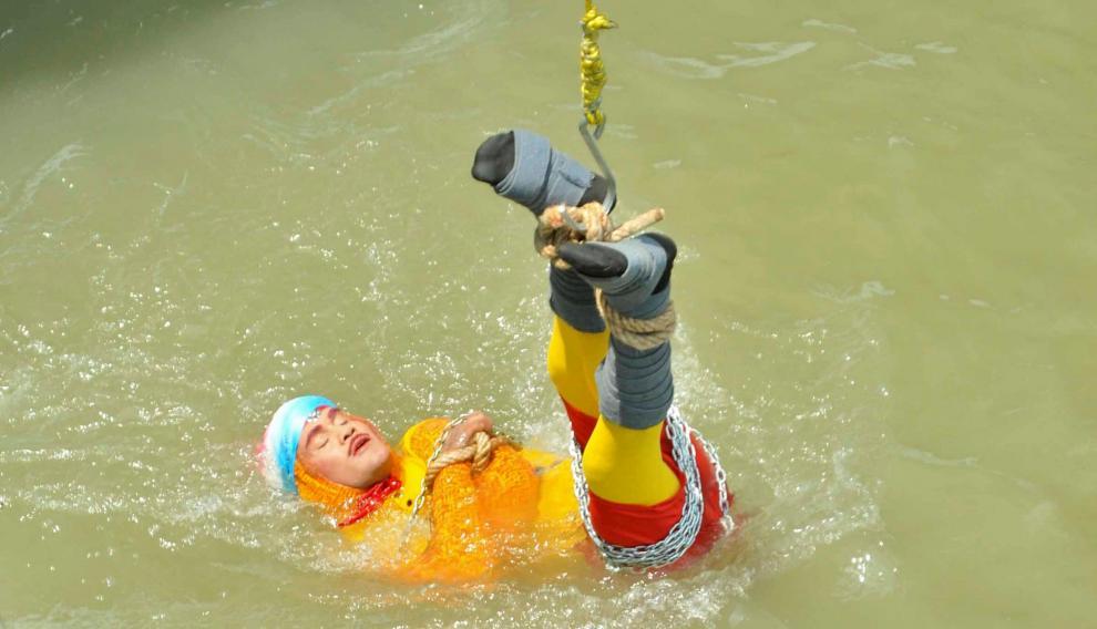 Chanchal Lahiri, conocido como el mago Mandrake, sumergiéndose encadenado en las aguas del Ganges