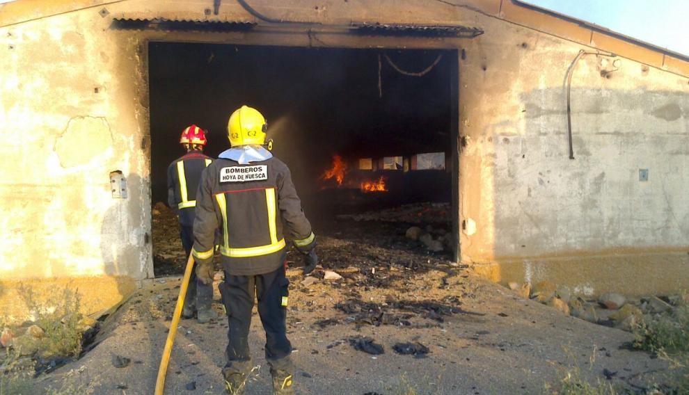 Bomberos en una de las naves agrícolas afectadas por el fuego.