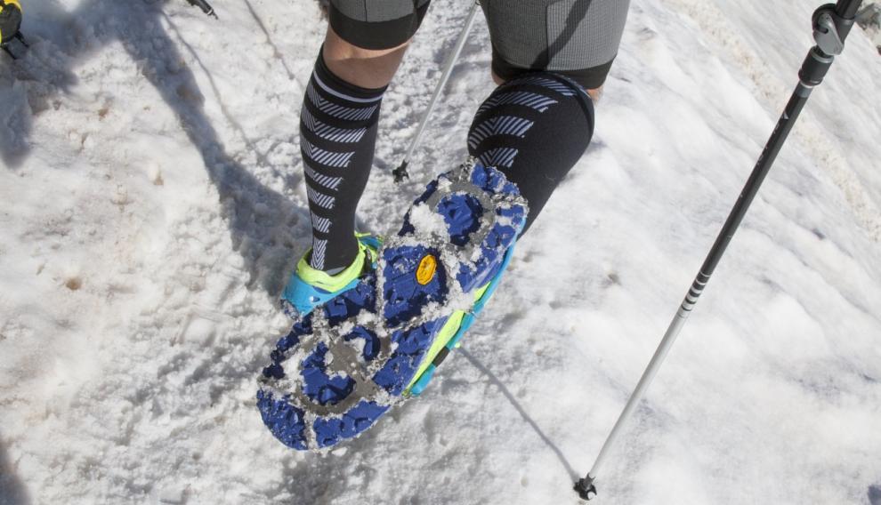 Crampones colocados en una zapatilla de trail.