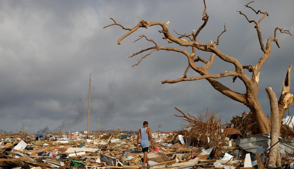 Un hombre anda sobre los restos de las viviendas arrasadas por Dorian en Bahamas