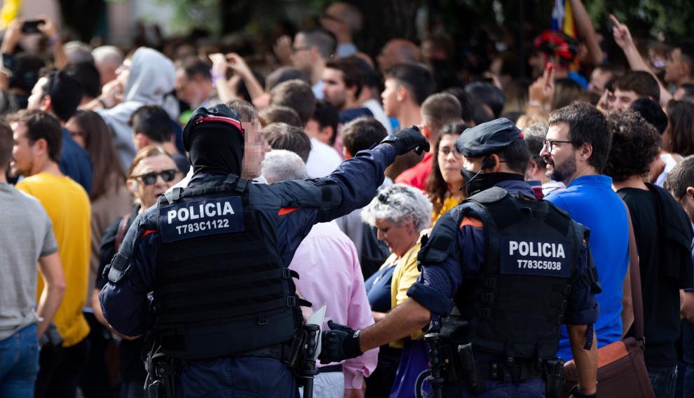 Los Mossos d'Esquadra controlan la multitud que se ha congregado junto al domicilio en el que se ha practicado un registro.