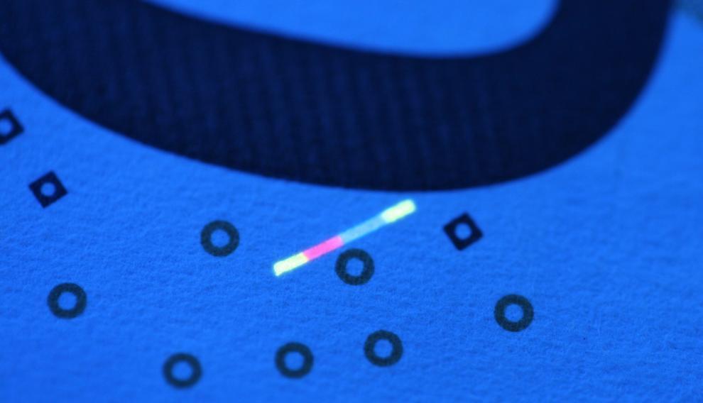 Inclusión fluorescente en un billete de 50 euros iluminado con luz ultravioleta de 365 nm. Tierras raras contra la falsificación.