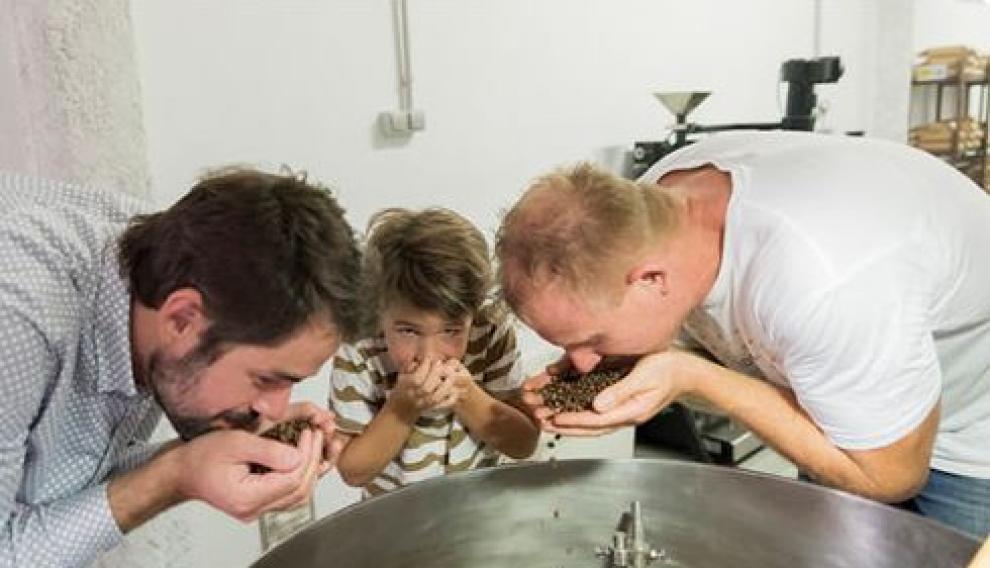 Luis Fernández, de la marca zaragozana Papa Largo, oliendo café con su hijo y el experto tostador Guido.