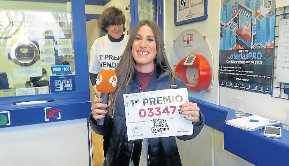 La periodista Lara Escudero, el año pasado, micrófono en mano y con el número del Gordo del que fue una de las agraciadas.