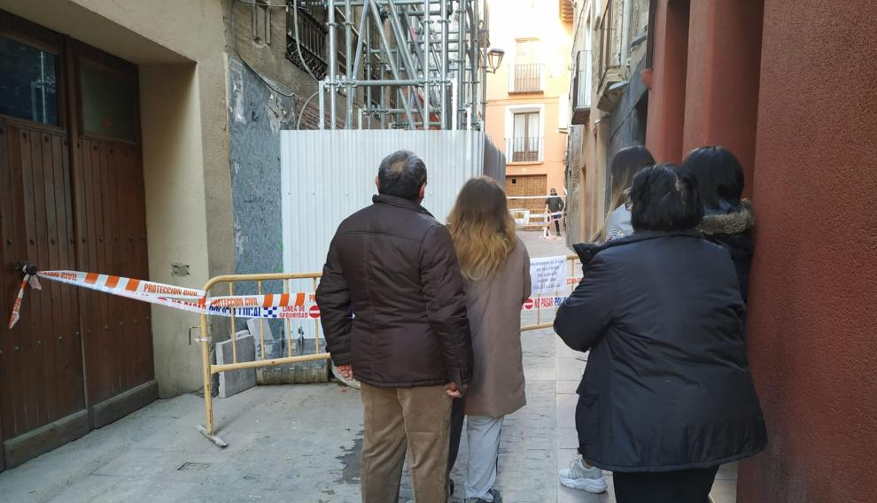 La familia afectada, junto a unas sobrinas, observa su vivienda derrumbada.