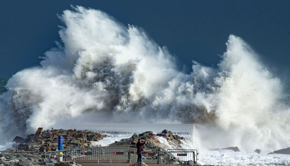 Una persona observa las impresionantes olas en la playa de Barceloneta, en Barcelona