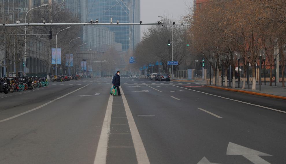 Un hombre con mascarilla camina por una calle desierta en Pekín