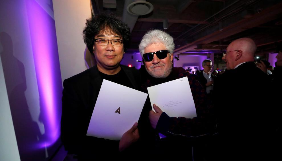 Bong Joon Ho y Pedro Almodovar, rivales y amigos, en una fiesta tras la ceremonia, muestan sus certificados de nominados.