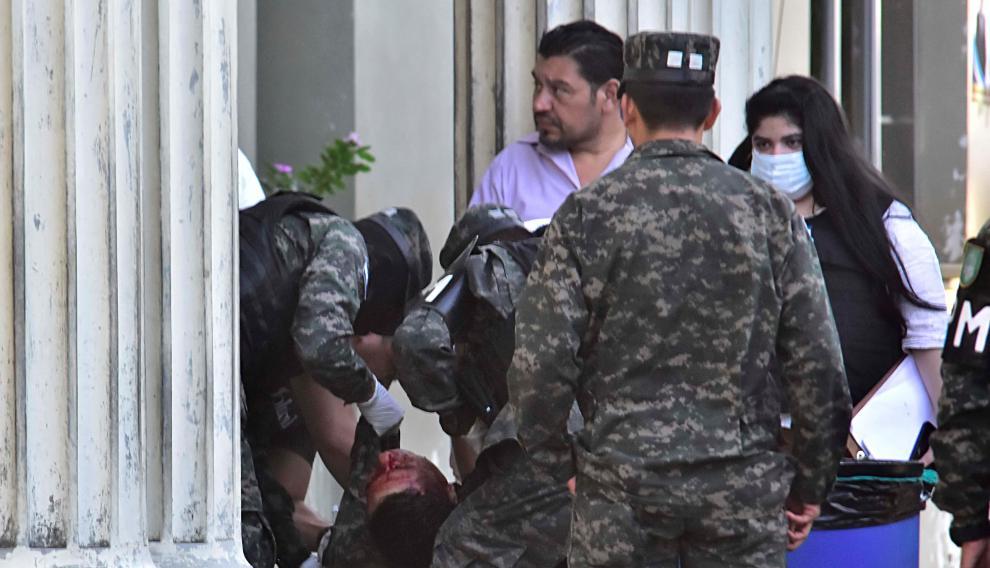 Varios compañeros sacan el cadáver de otro de los policías asesinados