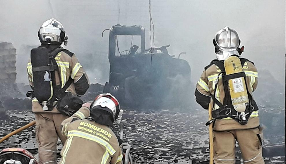 Tres bomberos de la DPZ frente a una máquina totalmente calcinada