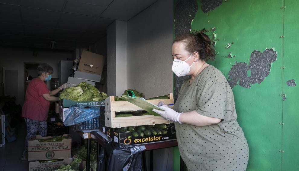 En una de las estancias de la asociación vecinal preparan la verdura que irá a los lotes de comida.