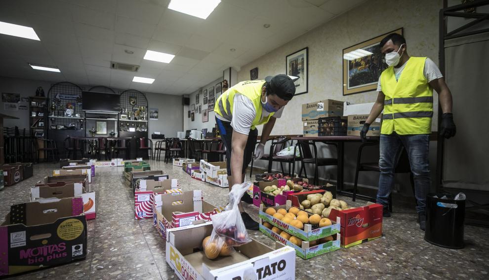 Las cajas con la comida ocupan el suelo del salón social de la sede de la Asociación de Vecinos Cívitas.