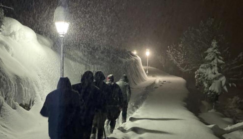 Foto de Tronchón ganadora del premio a la mejor foto tomada con teléfono móvil en el concurso de fotos de la Comarca del Maestrazgo. Un grupo de personas se dirigen en medio de la nevada a la ermita del Tremedal.