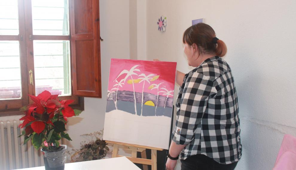 La zaragozana Pilar S., de 31 años, enseña uno de los cuadros que ha pintado en su piso del Actur, donde vive con otras tres compañeras con discapacidad.