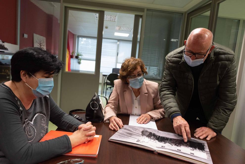 Manuel Morón les muestra a Nieves Borraz y Mercedes Abós imágenes de la riada de hace 60 años.