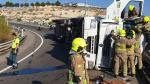Los bomberos rescatan al conductor de un camión que quedó atrapado tras volcar en la Z-40
