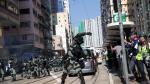 Un policía lanza una granada de gas contra manifestantes en una calle de Hong Kong.