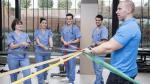 Trabajadores realizando ejercicios con banda elástica durante su jornada laboral.