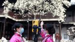 Tour guides wearing face masks show a blooming flower tree through a live-streaming platform, at a closed tourist attraction following the novel coronavirus outbreak in the country, in Yangzhou, Jiangsu