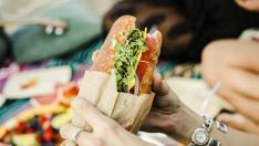 Woman eating a sandwich at the beach
