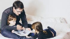 Niños y padre leyendo