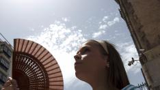 Una joven se refresca con un abanico