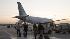 Varios viajeros se dirigen a un avión en el aeropuerto de Zaragoza.