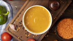 Red lentil soup in disposable cup bowl served with green vegetables. image