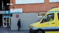A man walks past an ambulance as he leaves Hospital Carlos III, where a case of novel coronavirus has been confirmed, in Madrid