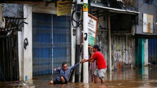 Un hombre mayor es ayudado tras las inundaciones en Yakarta (Indonesia).