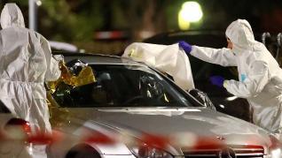 Los forenses cubren el cuerpo de uno de los fallecidos en el interior de un coche.