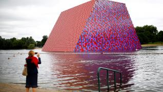 "FILE PHOTO: A woman photographs swimmers exercising in the Serpentine River in front of Christo's ""The London Mastaba"", in Hyde Park, London"