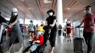 Travellers wearing protective gear are seen at the departure hall of Beijing Capital International Airport